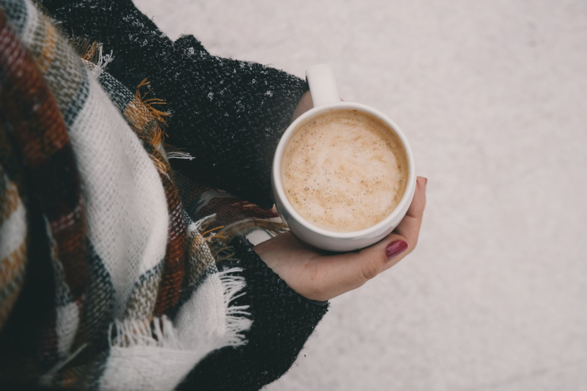Woman holding coffee in a winter setting